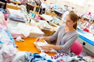A woman works in a clothing factory to show the kind of processes that go on there - successfully run a clothing business
