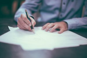man signing an agreement contract